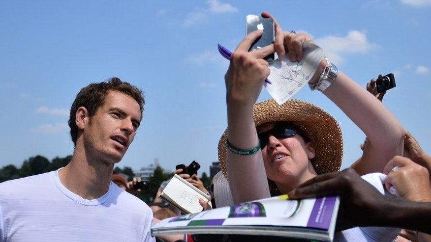 Andy Murray signs autographs for fans after training on day twelve of the Wimbledon Championships, at the All England Club, southwest London, on July 6, 2013, on the eve of his men's singles final against Novak Djokovic.