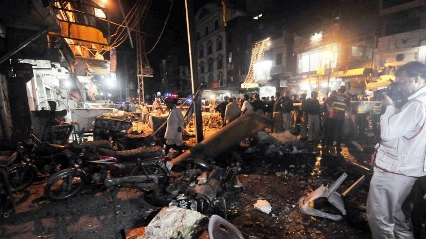 Pakistani police and volunteers search the site of bomb explosion on a food park in Lahore on July 6, 2013. Three people were killed and 38 injured on Saturday when a bomb exploded in a bustling food market in Pakistan's eastern city of Lahore, officials said.