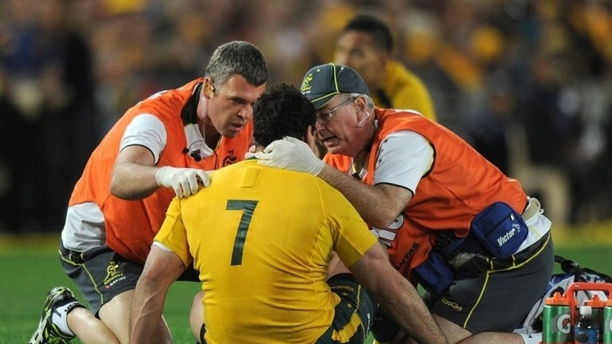 Wallabies' George Smith is checked by trainers after a heavy clash with the British and Irish Lions, in Sydney, on July 6, 2013. The visitors dominated from the start and they saw off an Australia fightback by running in three second-half tries to clinch the enthralling series 2-1.