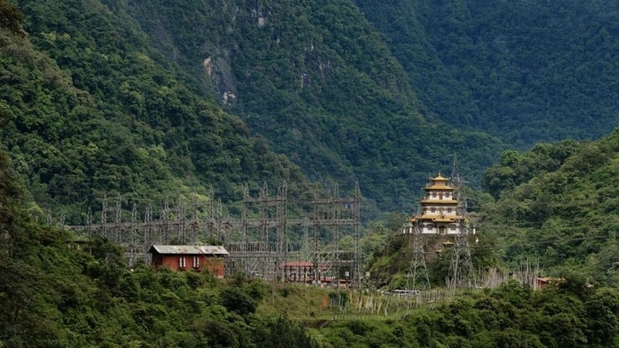 A Buddhist temple sits near an electricity grid main of the Chukha hydro power station in south-eastern Bhutan, on May 29, 2013. Home to meditating monks and Himalayan nomads, sleepy kingdom has set its sights on becoming an unlikely energy powerhouse thanks to its abundant winding rivers.
