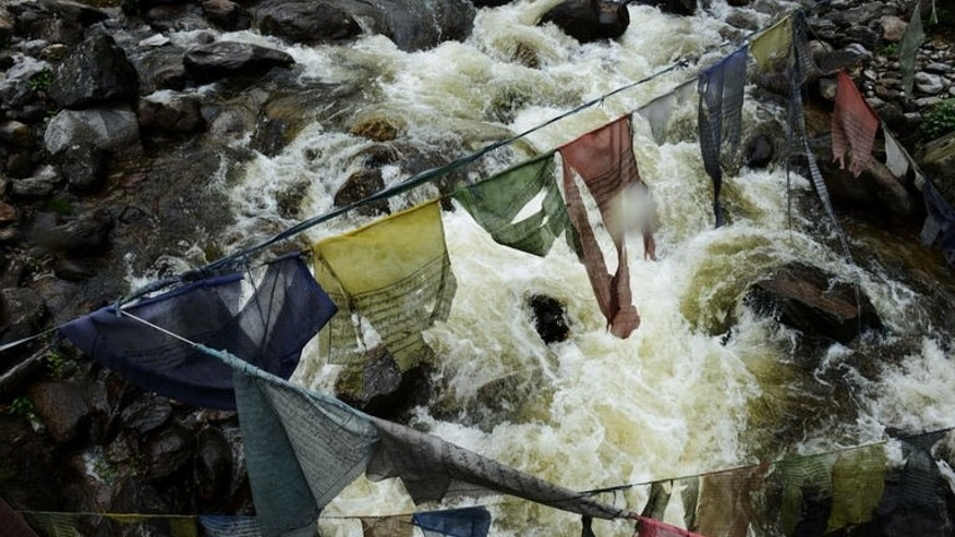 River flows under prayer flags on its way to the Chukha hydropower plant, in south-eastern Bhutan, on May 29, 2013. Home to meditating monks and Himalayan nomads, sleepy kingdom has set its sights on becoming an unlikely energy powerhouse thanks to its abundant winding rivers.