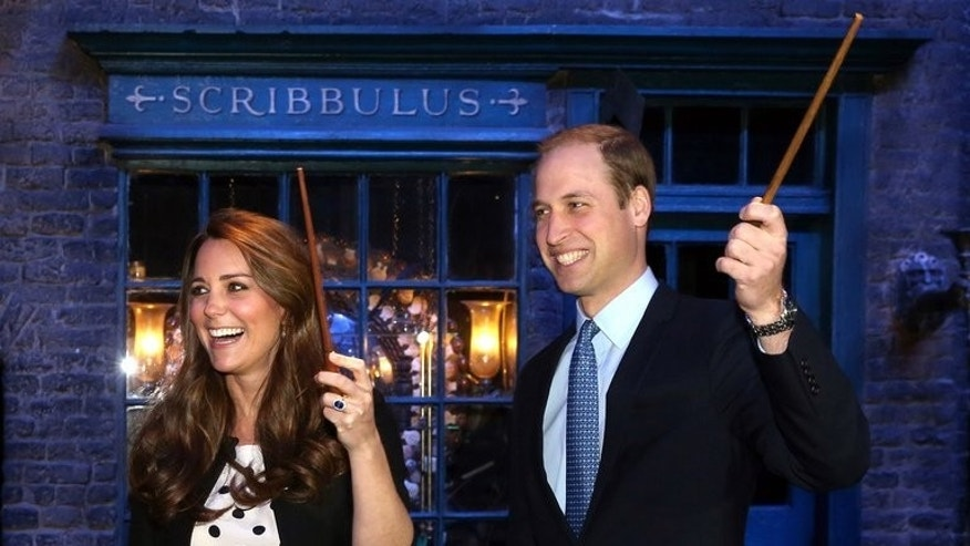 Britain's Prince William and his wife Catherine, Duchess of Cambridge, raise their wands on the set used to depict Diagon Alley in the Harry Potter films, on April 26, 2013. The imminent birth of Britain's royal baby will be announced on a golden easel and hailed by cannon fire -- but royal-watchers say behind the pomp William and Catherine will be trying to balance tradition with modern parenting