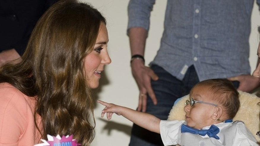 Catherine, Duchess of Cambridge (L) meets a child at Naomi House hospice in Sutton Scotney, Winchester on April 29, 2013. The imminent birth of Britain's royal baby will be announced on a golden easel and hailed by cannon fire -- but royal-watchers say that behind the pomp Prince William and Catherine will be trying to balance tradition with modern parenting.