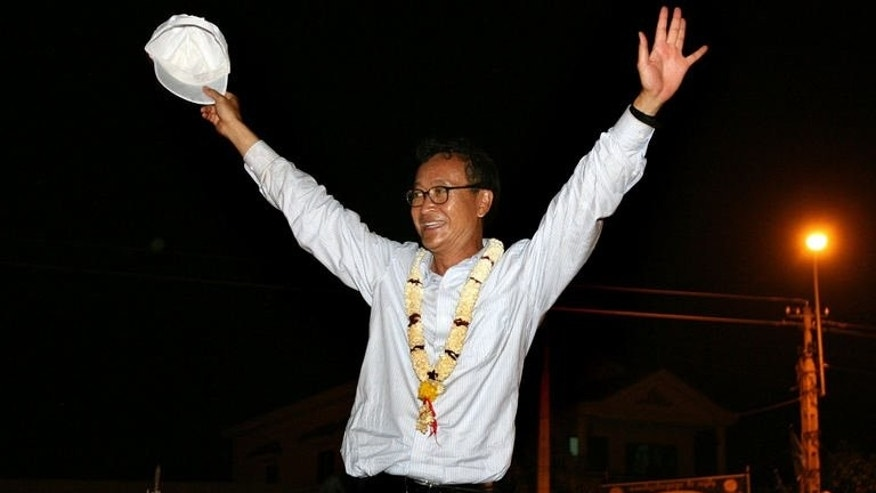 Cambodian opposition party leader Sam Rainsy greets supporters during an election campaign rally in Kampong Cham province, northeast of Phnom Penh, on July 24, 2008. Rainsy who lives in self-imposed exile abroad, has vowed to return to the country, in a move his party hailed on Sunday as a boost to its chances in elections this month.