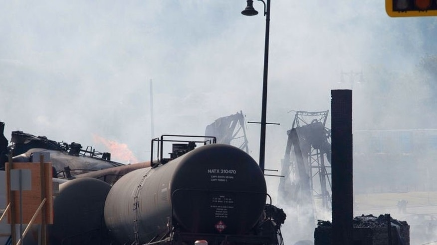 Wreckage continues to burn on July 7, 2013 after a freight train loaded with oil derailed July 6 in Lac-Megantic in Canada's Quebec province, sparking explosions that engulfed about 30 buildings in a wall of fire. Four bodies were found Sunday morning, bringing the official death toll from the disaster to five.