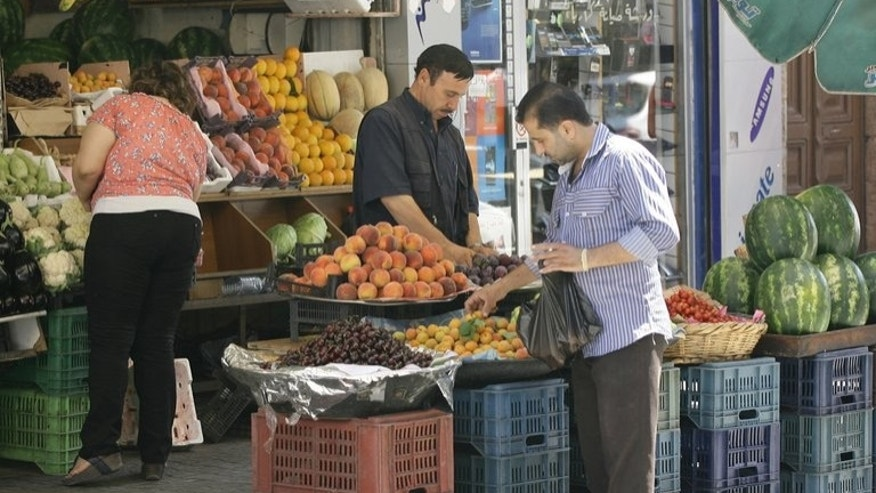 A Syrian man shops for fruit at a store in the capital Damascus, on June 30, 2013. Since the start of the conflict in Syria two years ago between rebel forces and pro-government troops, the Syrian economy has taken a tumble, affecting people from all walks of life.