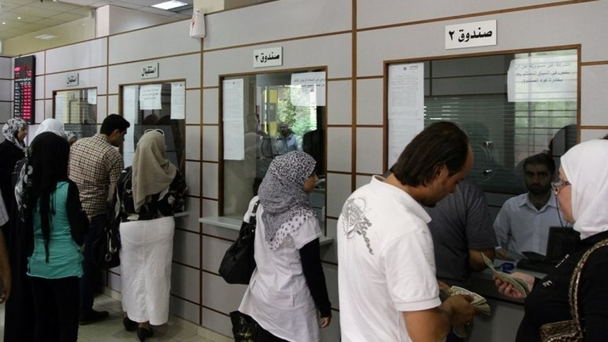 Syrians carry out transactions at a bank in the capital Damascus, on June 30, 2013. Since the start of the conflict in Syria two years ago between rebel forces and pro-government troops, the Syrian economy has taken a tumble, affecting people from all walks of life.