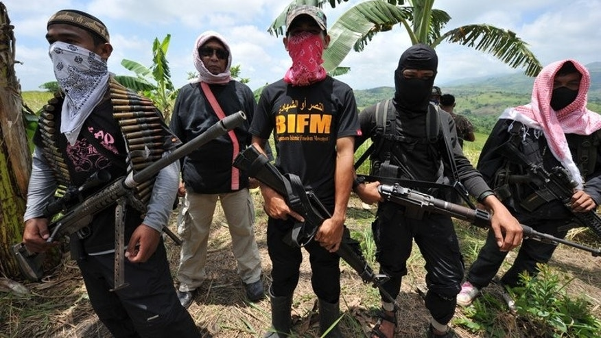 Members of the breakaway Muslim separatist group Bangsamoro Islamic Freedom Fighters (BIFF) stand guard during a clandestine press conference in the town of Datu Unsay, Maguindanao province, in the southern Philippines, on August 28, 2011. Five gov't soldiers and three BIFF rebels have been killed in clashes ahead of the resumption of peace talks aimed at ending a decades-old rebellion.