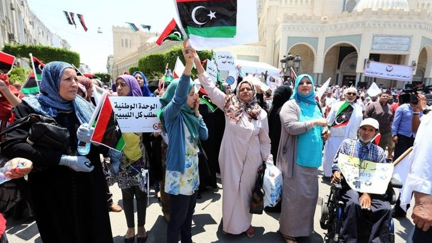"Libyan protesters wave national flags and hold placards during a demonstration in Tripoli's Algiers Square on July 7, 2013. Hundreds of demonstrators gathered in the Libyan capital on Sunday to demand the departure of militias and ""illegitimate brigades"" and the creation of an army and police force, an AFP journalist said."