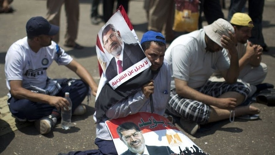 Egyptian supporters of the Muslim Brotherhood sit during a rally in support with deposed president Mohamed Morsi (featured on the posters) on July 6, 2013 outside Cairo's Rabaa al-Adawiya mosque.