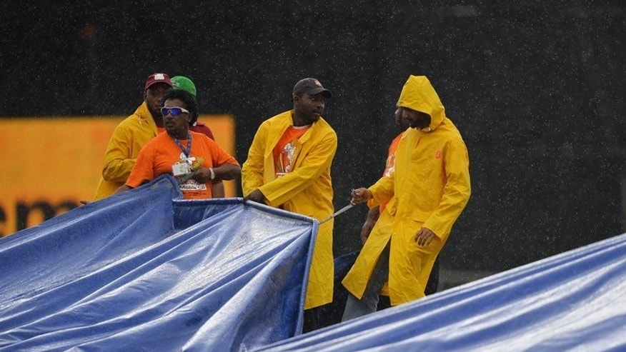 Groundsmen cover the field as rain interrupts the Sri Lanka-West Indies match in Port of Spain on Sunday. Rain has halted play in the fifth match of the Tri-Nation Series between the West Indies and Sri Lanka on Sunday.