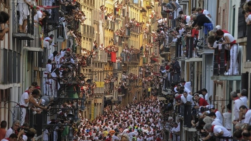 People watch the first bull run of the San Fermin Festival, on July 7, 2013, in Pamplona, northern Spain. Huge crowds of thrill-seekers got a scare as they fled half-tonne, sharp-horned fighting bulls charging through the city, resulting in four light injuries.