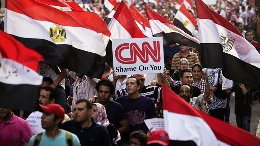 An Egyptian protester holds a placard against United States news channel CNN during a march towards Egypt's landmark Tahrir square against deposed President Mohammed Morsi on July 7, 2013 in Cairo, Egypt. Morsi's single year of turbulent rule was marked by accusations he failed the 2011 revolution that ousted autocratic president Hosni Mubarak by concentrating power in Islamist hands.