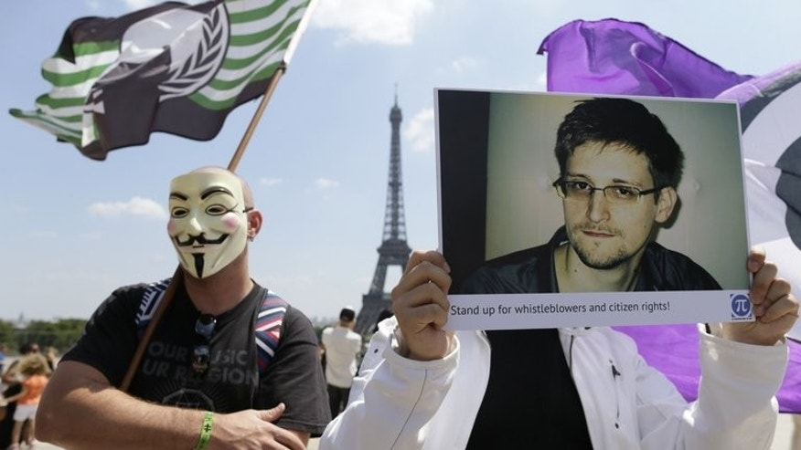 A demonstrator holds up a picture of Edward Snowden during a demonstration at the Place du Trocadero in front of the Eiffel tower in Paris on July 7, 2013. Snowden is a new kind of 21st century defector: not a top-level agent with a set of encrypted documents, but a computer geek armed with a portable hard drive.