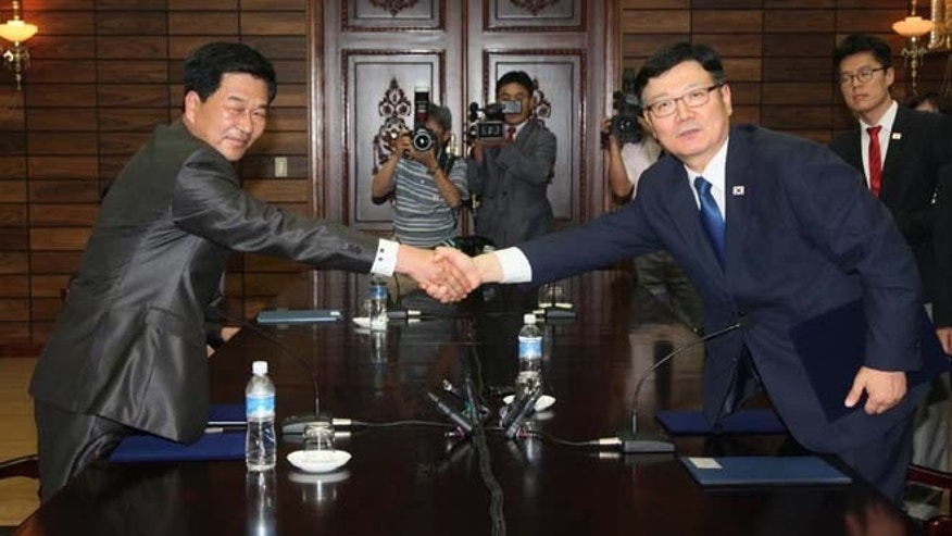 July 7, 2013: Suh Ho, the head of South Korea's working-level delegation, right, shakes hands with his North Korean counterpart Park Chol Su after exchanging documents on an agreement between the two sides during their meeting at Tongilgak in the North Korean side of Panmunjom which has separated the two Koreas since the Korean War. Delegates from North and South Korea held talks Saturday on restarting a stalled joint factory park that had been a symbol of cooperation between the bitter rivals.