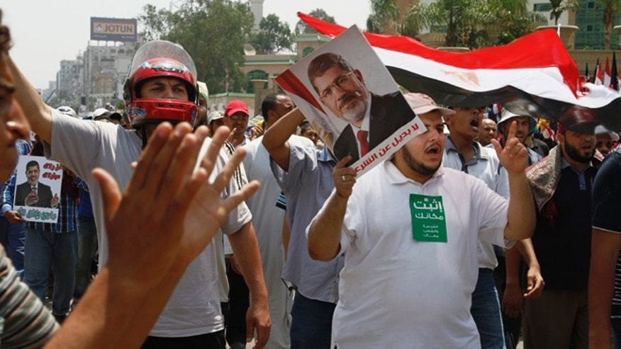 Supporters of Egypt's ousted President Mohammed Morsi wave Egyptian flags and his picture at a sit-in in Nasser City, suburb of Cairo, Egypt, Sunday, July 7, 2013. Egypt's new president moved to assert his authority and regain control of the streets Saturday even as his Islamist opponents declared his powers illegitimate and issued blood oaths to reinstate Mohammed Morsi, whose ouster by the military has led to dueling protests and deadly street battles between rival sides. (AP Photo/Paul Schemm)