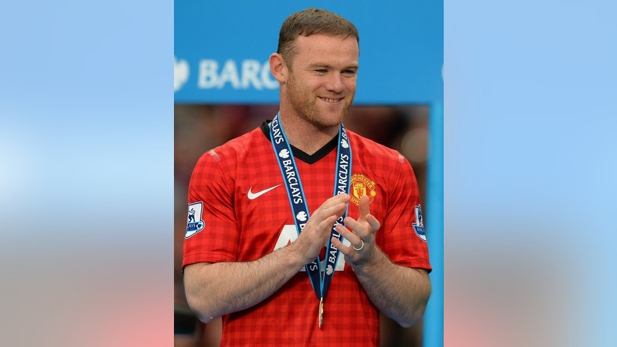 Wayne Rooney watches the presentation of the Premier League trophy at Old Trafford on May 12. Victoria Beckham, Wayne Rooney as well as actors Gerard Butler and Bradley Cooper will be taking their seats in Centre Court on Sunday in the hope of seeing history made.