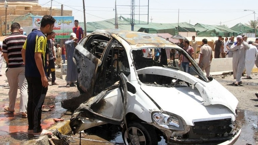 People inspect the site of a suicide car bomb attack in Al-Haq square in Samarra, a predominantly Sunni town north of Baghdad, on July 5, 2013. Two days of violence in Iraq left 19 dead, including six family members killed while returning from a wedding, police officers and doctors said on Monday.