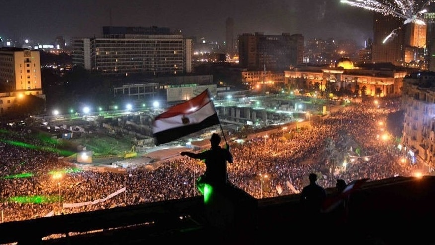 Egyptians wave the national flag on a building rooftop on July 7, 2013 in Cairo. Egypt's interim government is set to announce a new prime minister Monday, after hundreds of thousands of people rallied across the country in support of the military overthrow of president Mohamed Morsi.