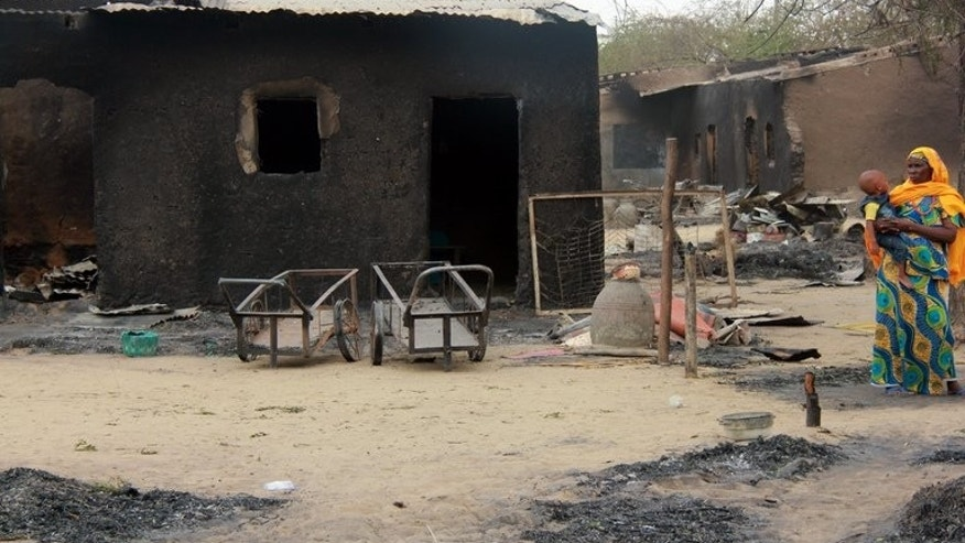 A woman stands near her burnt house in Nigeria's remote northeast town of Baga on April 21, 2013 after two days of clashes between officers and members of the Nigerian-based Islamist extremist group Boko Haram. The group is to be banned in Britain under anti-terror laws, the British interior ministry announced on Monday.