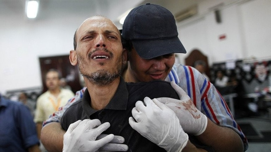 A man grieves at a makeshift hospital where victims were brought following clashes between Egyptian police and Muslim Brotherhood supporters outside the Republican Guard in Cairo early on July 8, 2013.