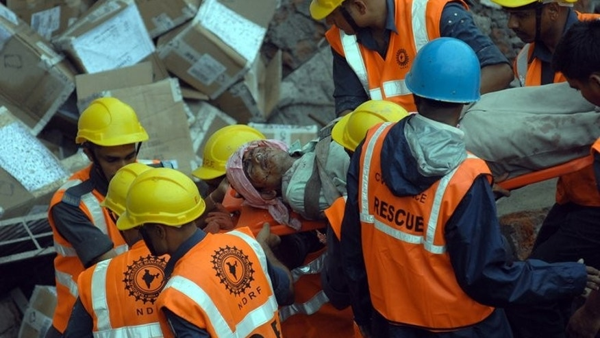 Rescue personnel move an injured worker from the rubble of a collapsed building in Mumbai on July 4, 2013. A two-storey hotel collapsed in the southern Indian city of Secunderabad, killing five restaurant workers and injuring 15 others.