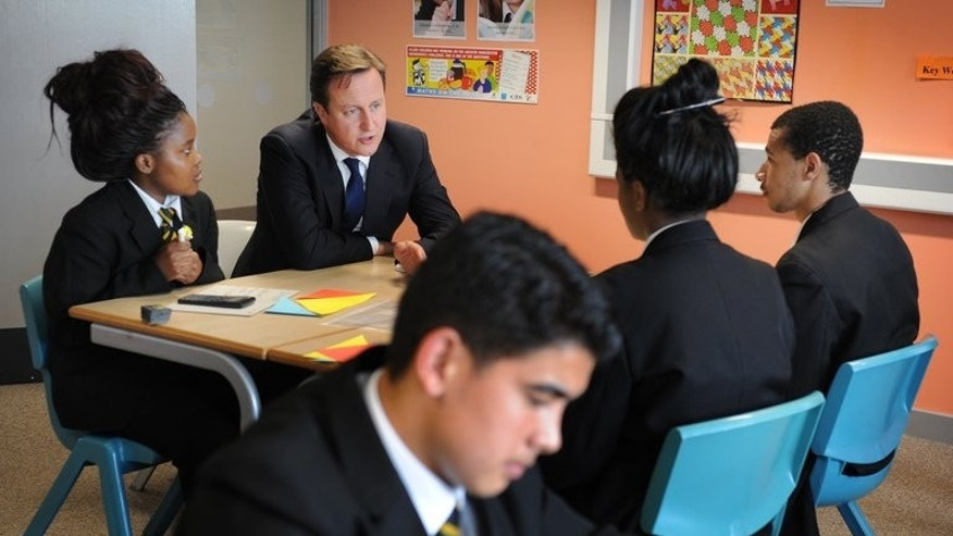 British Prime Minister David Cameron (second left) speaks to students in a mathematics class at Cedar Mount high school in Gorton, Manchester on October 4, 2011. Children will learn to write computer programmes and study internet safety from their first two years of school under a revised national curriculum unveiled Monday.