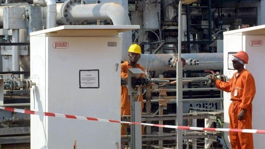 This file photo shows two workers at an oil plant in Rabi, northwestern Gabon, pictured on June 27, 2003. Gabon has taken the exceptional step of withdrawing the right of Addax Petroleum, a subsidiary of Chinese oil giant Sinopec, to exploit an oilfield, raising concerns over possible repercussions on the business climate.