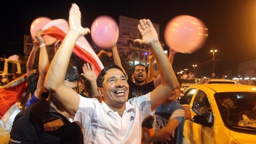 An Iraq man celebrates in the streets of Baghdad after the Iraq Under 20 football team beat South Korea on July 7, 2013. Iraqis sung, danced and fired guns in the air, celebrating a victory over South Korea in the U-20 World Cup, a small bright spot in the months-long surge in violence plaguing the country.