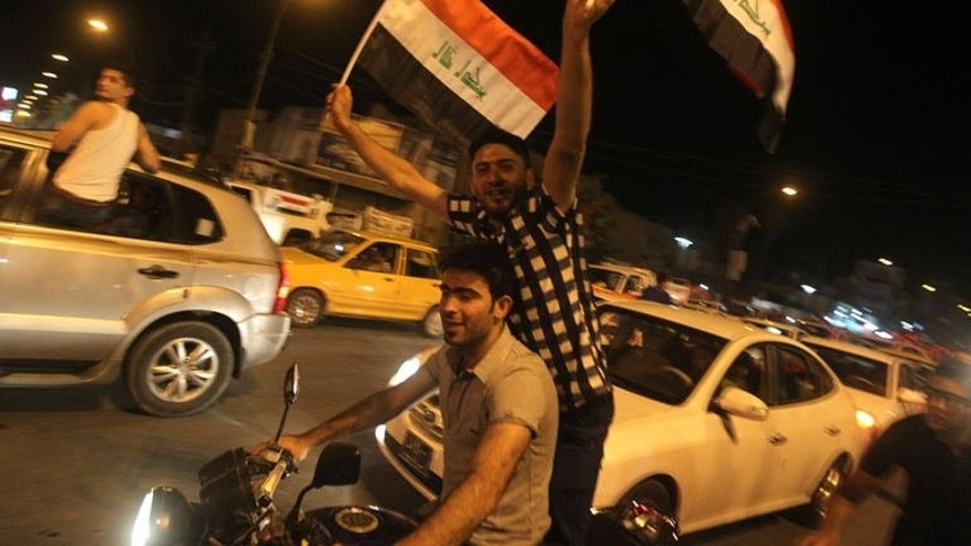 Iraqis celebrate in the streets of Baghdad after the Iraq Under 20 football team beat South Korea, on July 7, 2013.