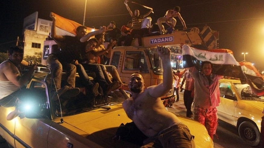 Iraqis celebrate in the streets of Baghdad after the Iraq Under 20 football team beat South Korea on July 7, 2013.