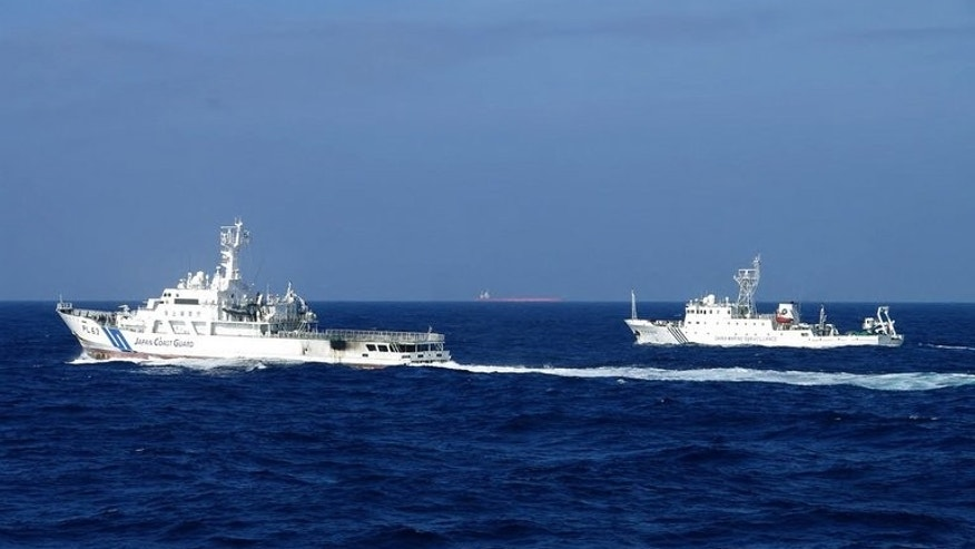 "A Chinese marine surveillance ship (R) alongside a Japan Coast Guard vessel near disputed islets on February 4, 2013. China's ""coercive"" behaviour in the waters around the land mass could trigger an incident, Tokyo said in a new defence paper."