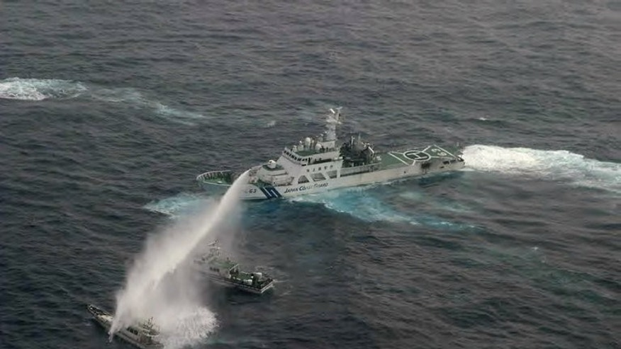 A Japan Coast Guard vessel (R) sprays water at a Taiwanese boat near disputed islands on January 24, 2013. China claims the Japan-controlled islets, as does Taiwan.
