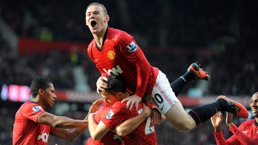 Manchester United's English forward Wayne Rooney celebrates after Dutch teammate Robin van Persie scored against Arsenal during an English Premier League game at Old Trafford in Manchester, northwest England, on November 3, 2012. English Premier League champions United on Monday announced that it had signed a five-year partnership with Russian airline Aeroflot.