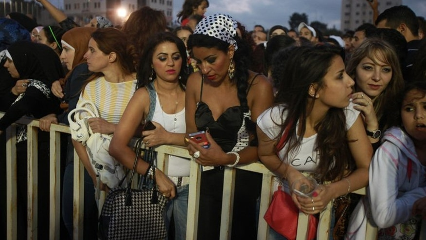 "People attend a concert by ""Arab Idol"" winner Mohammed Assaf in the West Bank city of Ramallah on July 1, 2013. Assaf made his debut appearance in Ramallah on July 1, playing to a crowd of 40,000 fans, although the gig was cut short over fears the crowd might storm the stage."