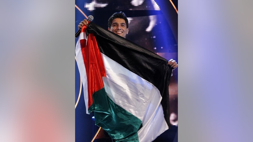 "Mohammed Assaf celebrates with his national flag after winning ""Arab Idol"" in Zouk Mosbeh, Lebanon on June 23, 2013. His victory sparked unprecedented jubilation across the Palestinian territories, the celebrations continuing in the West Bank last week."