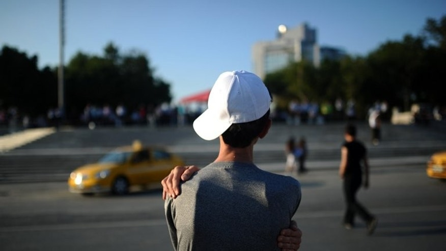 A man looks to Gezi park in Istanbul on June 18, 2013. Turkish riot police fired rubber bullets, tear gas and water cannon to block demonstrators from entering a small Istanbul park, the birthplace of deadly unrest that engulfed the country last month.