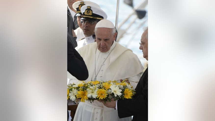 """Pope Francis casts a wreath into the sea off Italy's Lampedusa island on July 8, 2013. He called for an end to """"indifference"""" to the plight of refugees on the island where tens of thousands of migrants from Africa and the Middle East first reach Europe."""