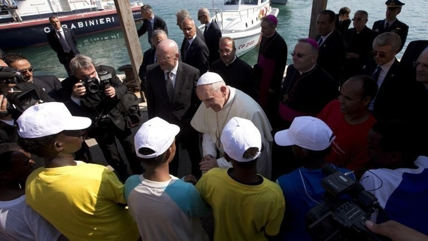 "Pope Francis (C) greets migrants during his visit to the Italian island of Lampedusa, on July 8, 2013. He called for an end to ""indifference"" to the plight of refugees on the island where tens of thousands of migrants from Africa and the Middle East first reach Europe."