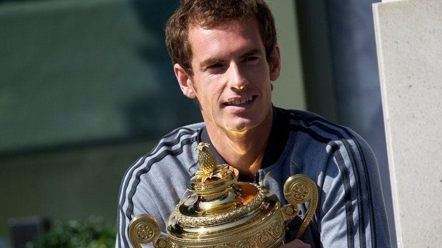 British tennis player Andy Murray poses with the 2013 Wimbledon trophy at the All England Club in Wimbledon, southwest London, on July 8, 2013. More than a quarter of the British population tuned in to watch Andy Murray become Britain's first men's Wimbledon champion since 1936, BBC figures released Monday showed.