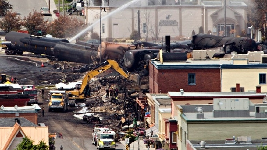 July 8, 2013: Searchers dig through the rubble for victims of the inferno in Lac-Megantic, Quebec as firefighter continue to hose down tanker cars to prevent explosions.