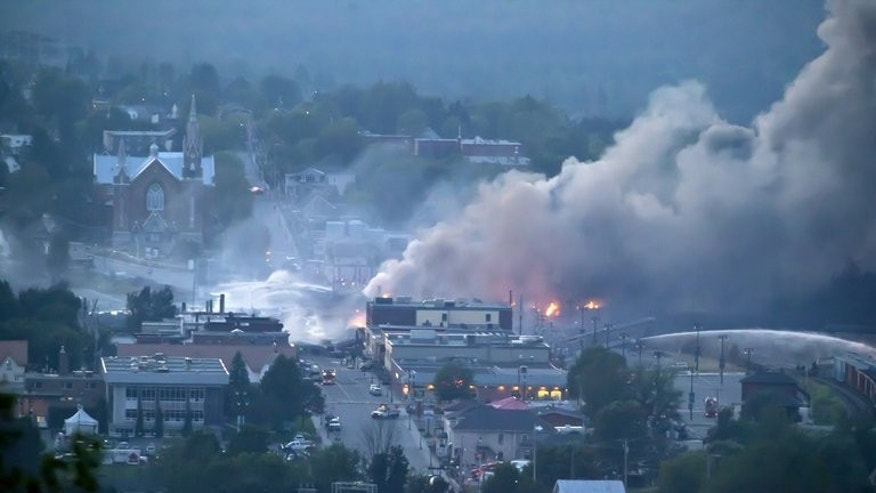 Firefighters douse blaze after a freight train, loaded with oil, derailed in Lac-Megantic, in Canada's Quebec province, on July 6, 2013, sparking explosions and fire that leveled more than four blocks, including 30 buildings, and forced about 2,000 people to flee the town.