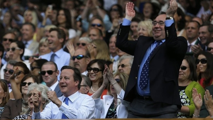 British Prime Minister David Cameron (left) and Scotland's First Minister Alex Salmond (right) celebrate as Britain's Andy Murray beats Serbia's Novak Djokovic in the men's singles final of the 2013 Wimbledon Championships on July 7, 2013. Salmond has scoffed at suggestions he sought to gain political profit from Andy Murray's Wimbledon win by brandishing a Scottish Saltire flag.