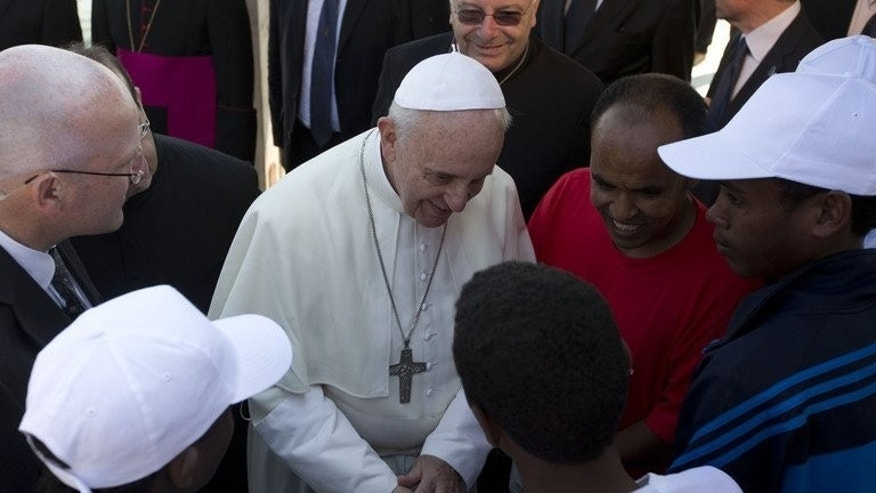 Pope Francis greets migrants during his visit to Lampedusa, a key destination for immigrants from Africa, on July 8, 2013. The pope has called for an end to indifference to the plight of refugees around the world.
