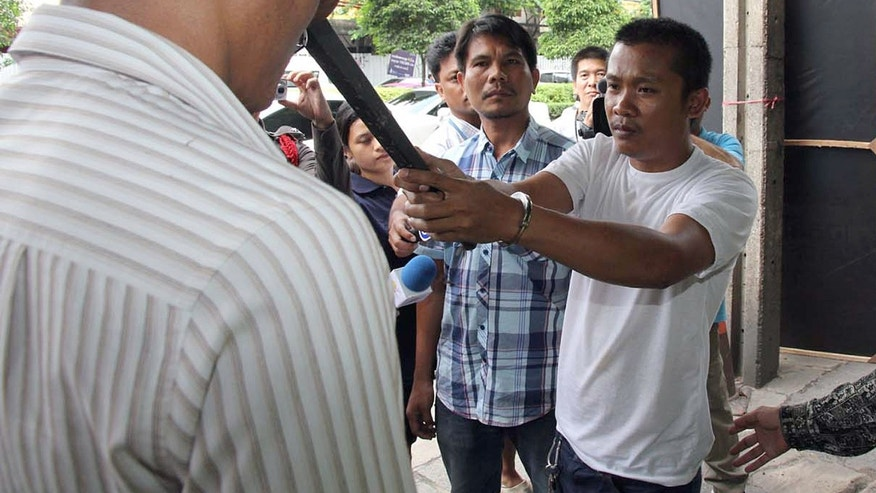 July 7, 2013 - Chidchai Utmacha, right, a Thai taxi driver shows how he stabbed an American passenger, Troy Lee Pilkington, during a police re-enactment in Bangkok, Thailand.  Thai police arrested Chidchai accused of stabbing Pilkington to death in an argument over a fare worth less than $2.