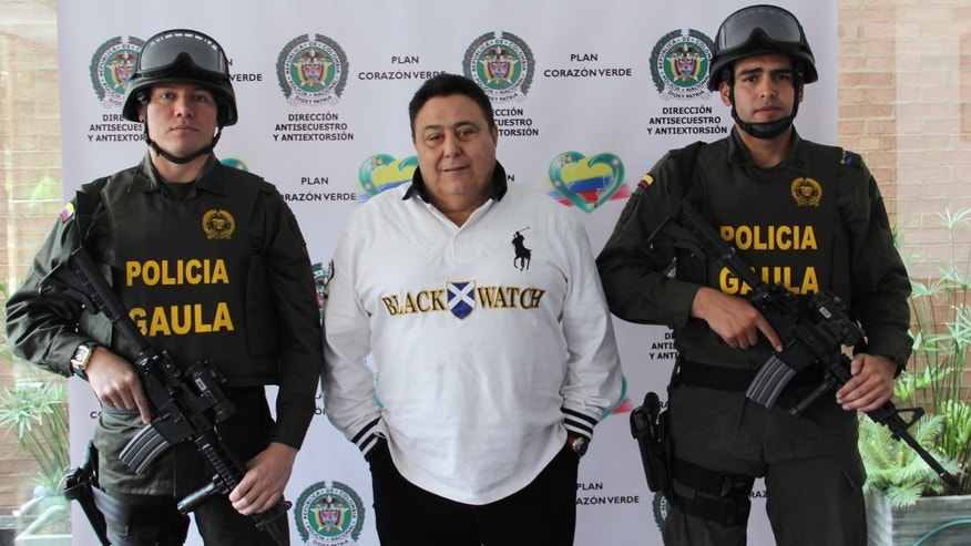 Colombian police officers flank alleged Italian drug trafficker Roberto Pannunzi at a police station in Bogota, July 6, 2013.