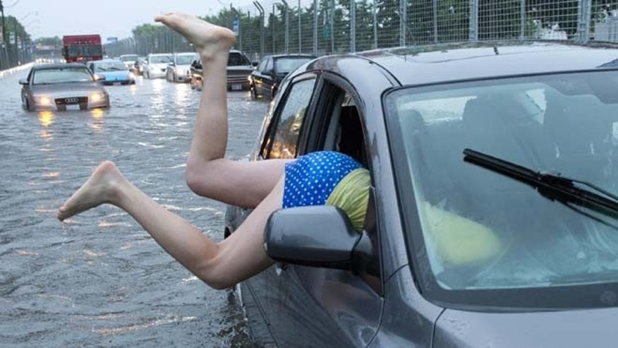July 8, 2013: A woman gets back into her flooded car on the Toronto Indy course on Lakeshore Boulevard in Toronto