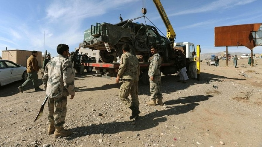 Afghan police remove a damaged vehicle following a roadside bomb explosion on the outskirts of Herat, on November 12, 2011. A Taliban bomb in western Afghanistan has killed ten women and one man travelling in a three-wheel vehicle, Afghan police told AFP.