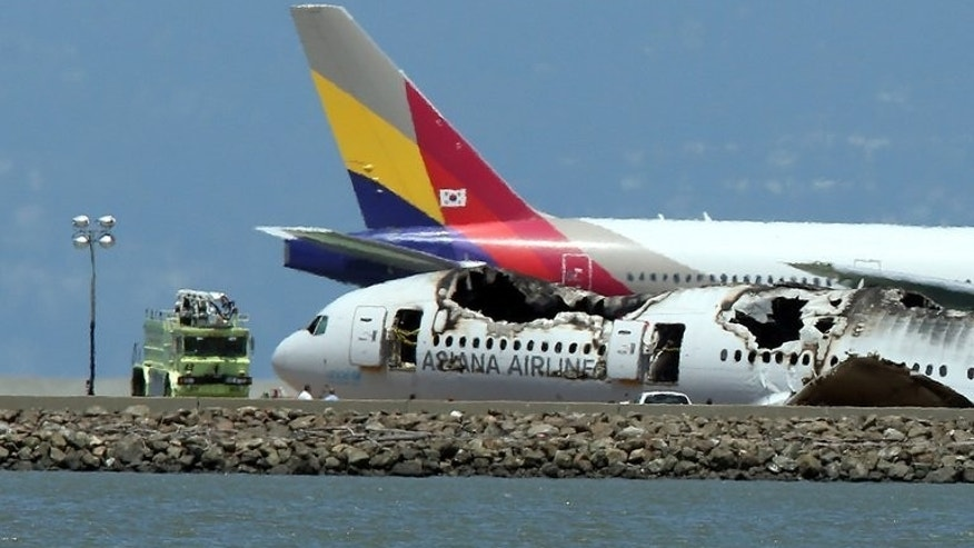"An Asiana Airlines flight enroute to South Korea taxis past the wreckage of flight 214 as it sits on the runway of San Francisco International Airport on July 8, 2013 in California. Asiana Airlines has defended the pilots of the crashed jet as ""very competent"" as attention focussed on whether human error caused the Boeing 777 to slam into the runway."