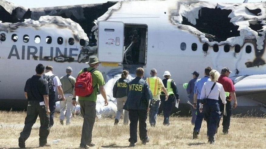 Investigators inspect the wreckage of Asiana Flight 214 in San Francisco, July 7, 2013. Investigators probing the Asiana Airlines plane crash began interviewing cockpit crew of the Boeing 777 amid mounting indications that pilot error may have caused the fatal accident.
